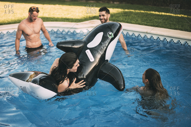 Friends swimming on inflatable toy in pool