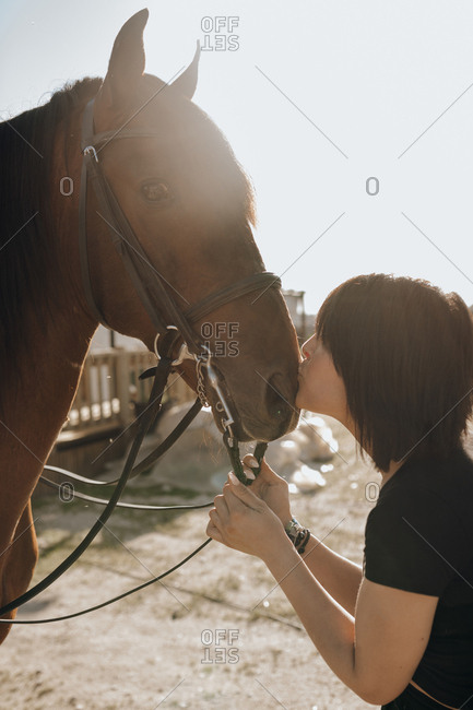 Young woman with closed eyes kissing horse while spending time on ranch on sunny day