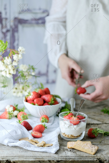 Faceless chef using fresh juicy tasty strawberries while preparing creamy sweet dessert