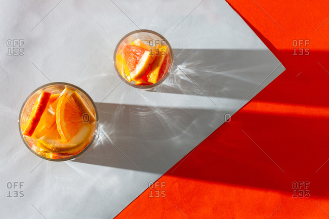 From above fresh slices orange and lemon in glass cups cast shadow on white orange background