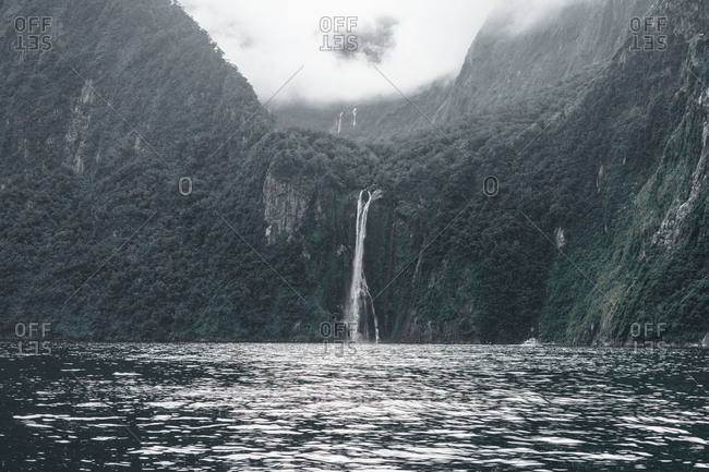 Amazing waterfall with powerful stream flowing from cliffs on rocks in Milford sound New Zealand