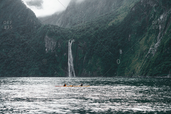 Red canoes float on dark green river surrounded by hilly bushy mountains in Milford sound New Zealand