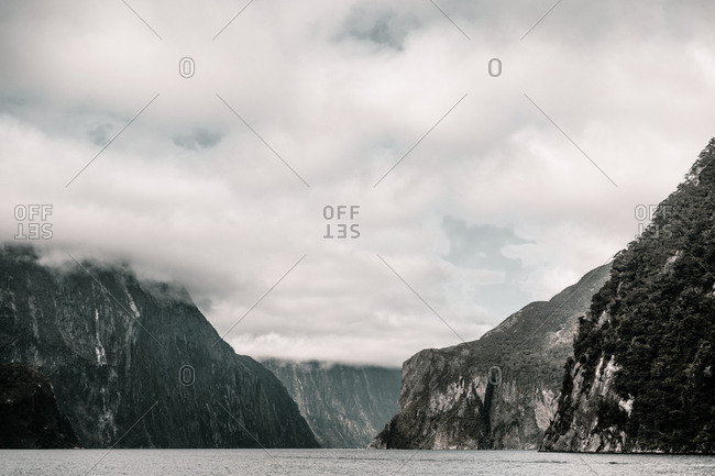 amazing lake between rocky mountains in clouds in Milford sound New Zealand