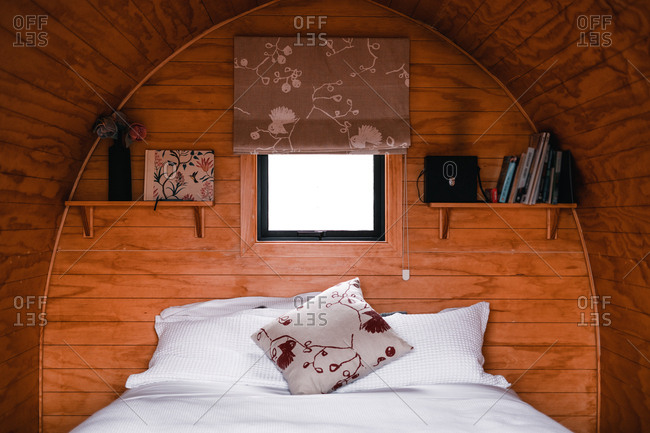 Comfortable bedroom in wooden pod with small window in Te Wepu Intrepid Pods New Zealand
