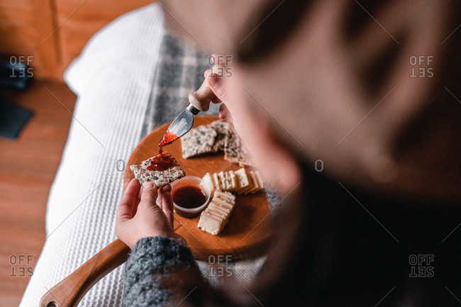 Crop view of woman hand taking delicious snack of cheese with crackers and marmalade on wooden board on bed