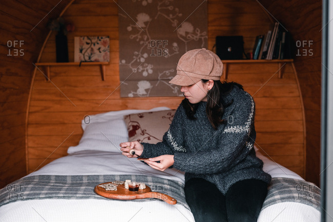 Young woman in warm clothes eating crackers sitting on bed in wooden cabin in Te Wepu Intrepid Pods New Zealand
