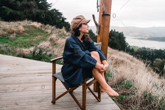 Young woman in bath robe sitting outside and looking away in Te Wepu Intrepid Pods New Zealand