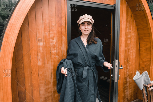 Young woman in bath robe stepping out of a wooden cabin and looking at camera in Te Wepu Intrepid Pods New Zealand