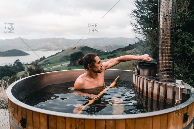 Young man bathing in private wood-fired hot tub holding a wooden oar in Te Wepu Intrepid Pods New Zealand