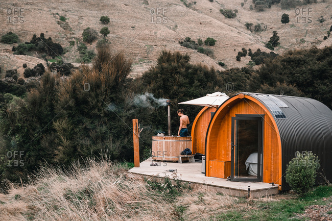 Intrepid pods for rest and hot tub with shirtless young man in Te Wepu New Zealand