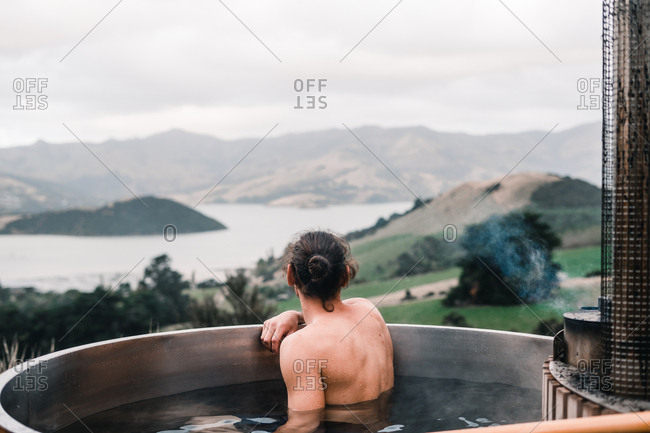 Back view of anonymous young man bathing in private wood-fired hot tub in Te Wepu Intrepid Pods New Zealand