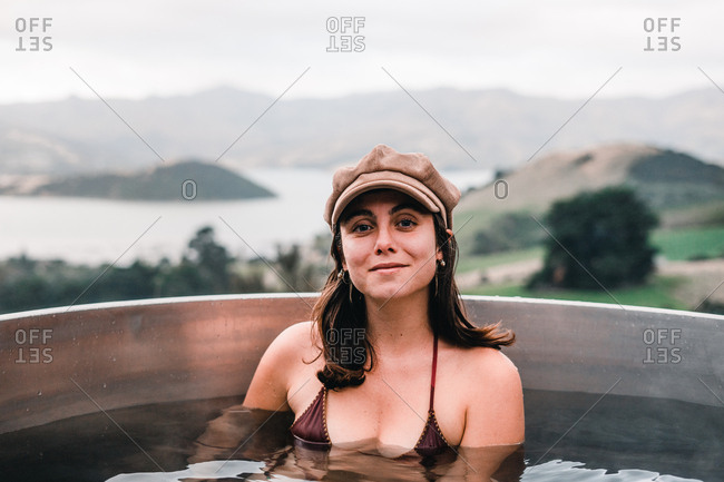Young woman in cap and bikini bathing in private wood-fired hot tub and looking at camera in Te Wepu Intrepid Pods New Zealand