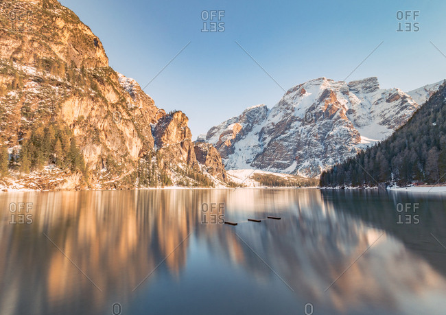 Breathtaking landscape with magical reflection of rocky mountains in crystal lake water in bright sunny day