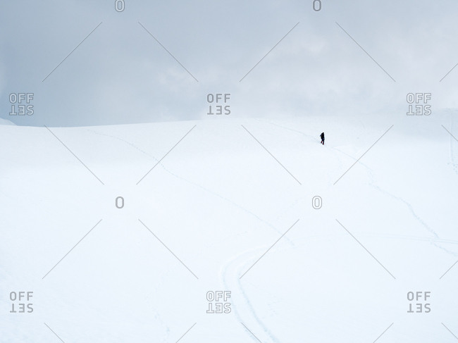 Person standing in the distance on a cold snowy hill