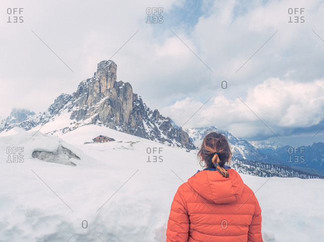 Back view of young woman in orange warm jacket looking at majestic snowy mountain landscape in cloudy day