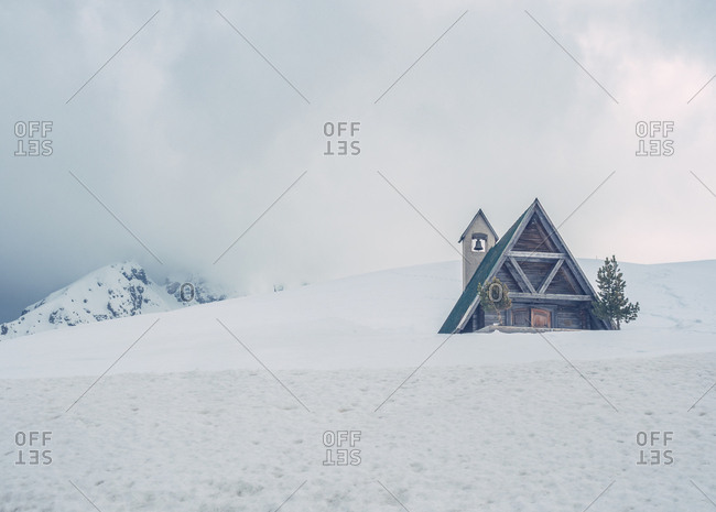 Amazing landscape with wooden turquoise triangular roof house and trees on snowy white hill