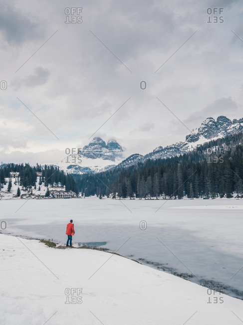 Unrecognizable person standing in snow surrounded by forest and mountains