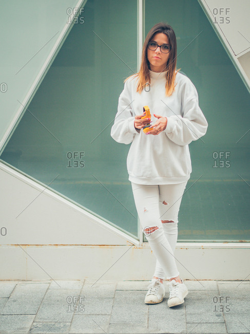 Young dreamy modern female hipster in casual white clothes with bright yellow headphones on background of wall