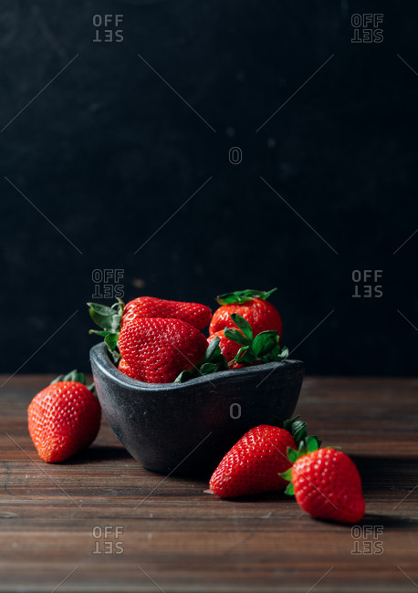Fresh ripe strawberries in black concrete bowl on wood background