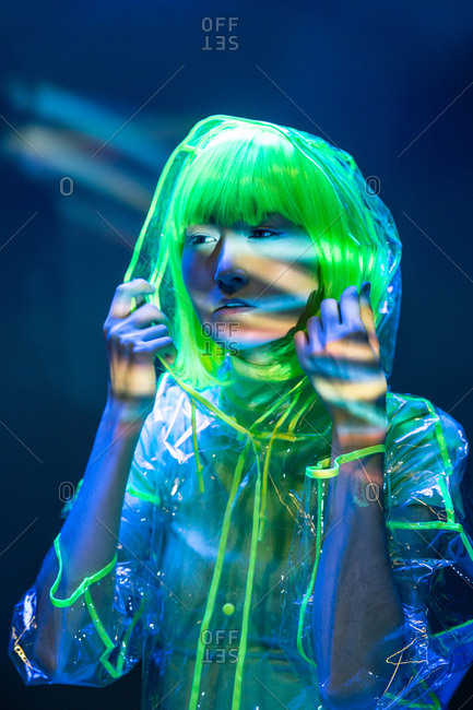 Young Asian woman in yellow wig and transparent plastic wear posing in fluorescent light with raised hands