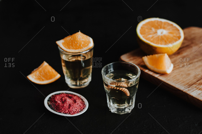 Shots of traditional Mexican mezcal served with larva an citrus near empty bottle against black background