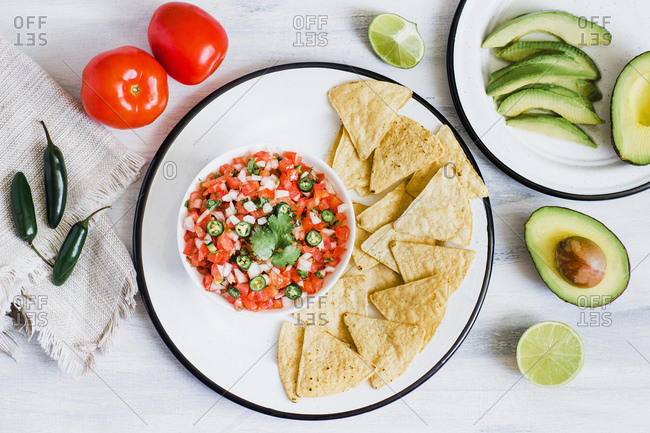From above fresh sauce of crushed tomatoes onions and chili Pico de Gallo with chips and sliced avocado on plates on white wooden table