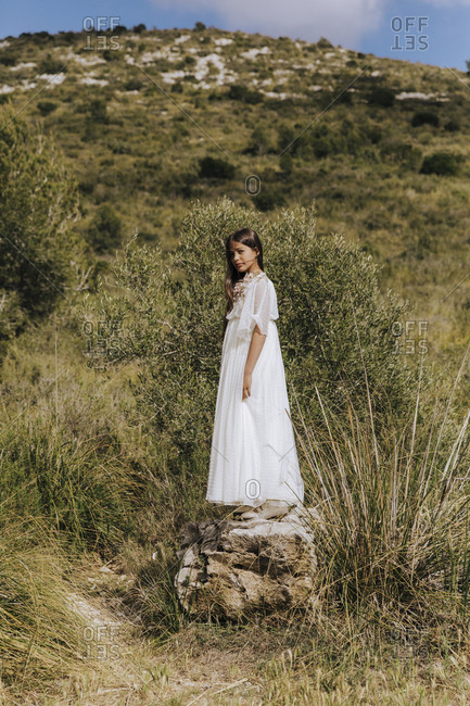 Cheerful pretty long haired girl lush white dress standing on stone in mountains in light cloudy day