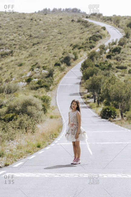 Stylish pretty girl in white lush dress walking on road in mountains