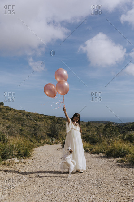 Stylish pretty girl in long lush white dress with red balloons and white puppy standing on road in mountains