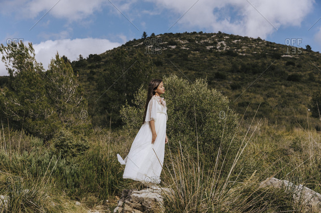 Pretty long haired girl lush white dress standing with closed eyes on stone in mountains in light cloudy day