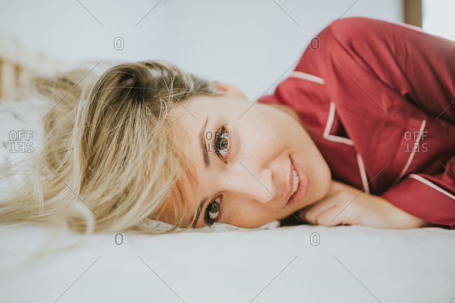 Cheerful young pretty woman in pajamas smiling on bed in bedroom