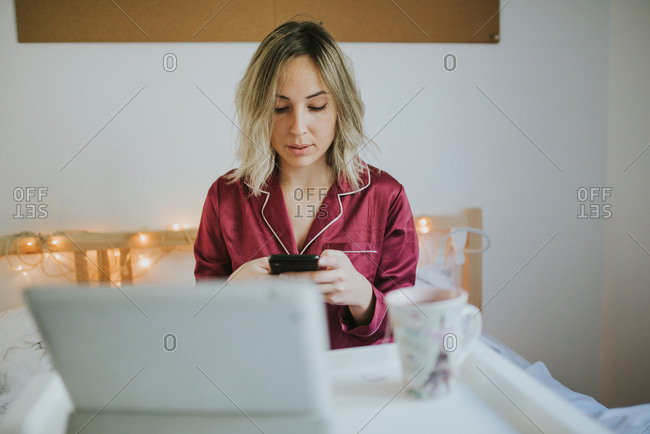 Young pretty woman in pajamas on tablet looking in smartphone while sitting in bed with coffee and table tray
