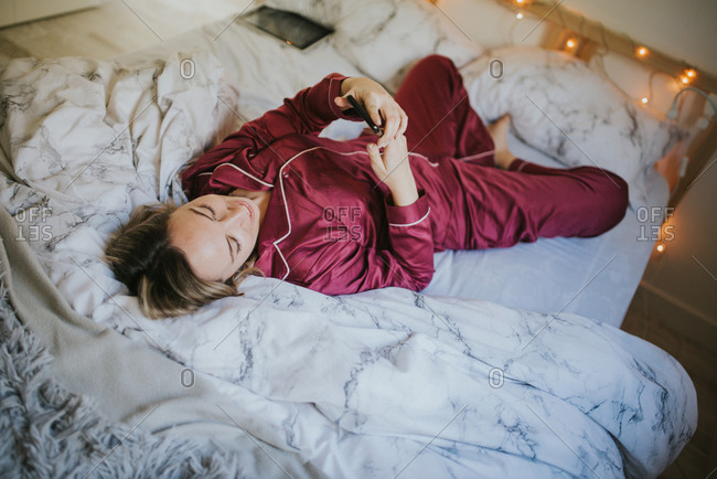 Young pretty woman in pajamas lying down on bed looking at smartphone
