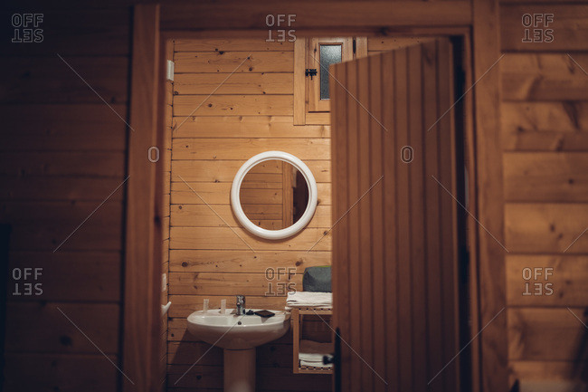 Cozy bathroom in wooden house with opened door and modern equipment