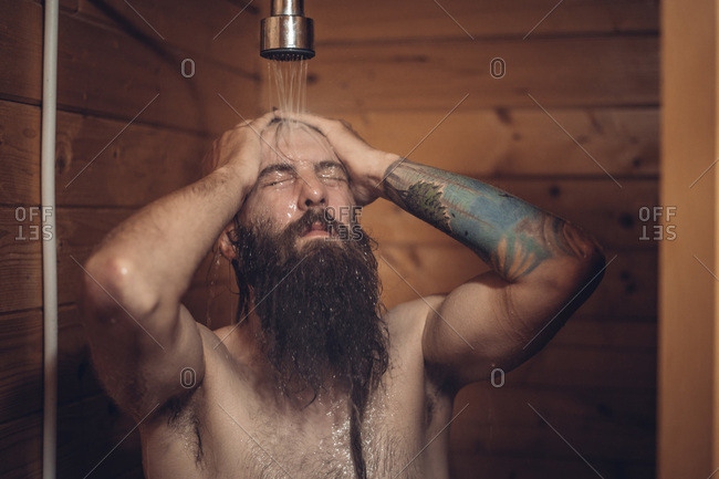 Middle aged bearded man with tattoo taking shower in wooden bathroom