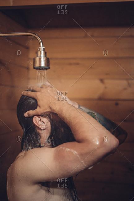 Man taking shower in wooden bathroom