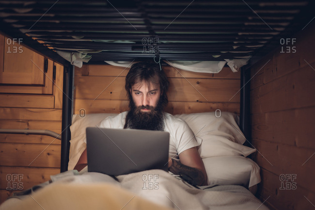 Man using laptop in rustic bunk bed