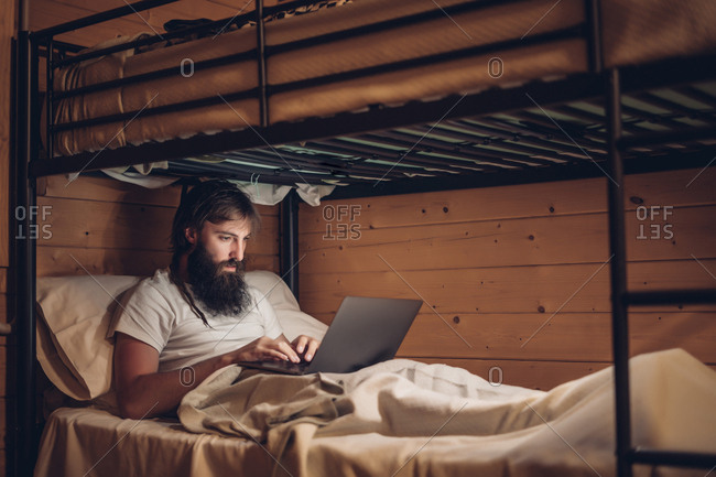 Concentrated bearded hipster working on laptop while lying in simple bunk bed of country wooden house