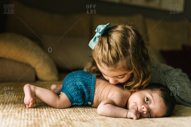 Cute little girl kissing innocent newborn baby in back lying on sofa at home