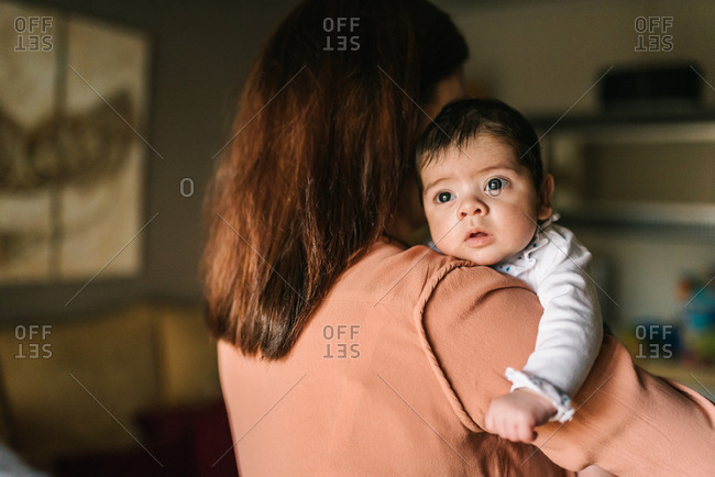 Back view unrecognizable brunette mom hugging cute little baby looking away at home