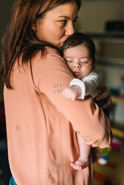 Back view brunette mom hugging cute little baby looking away at home