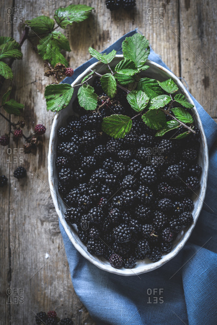 From above tasty fresh blackberries serving in bowl on wooden background with blue napkin