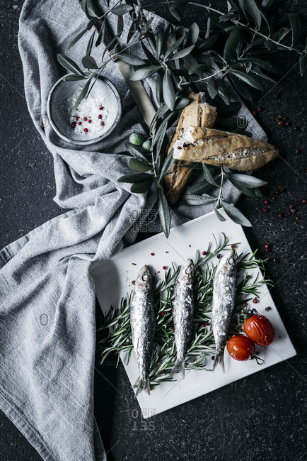 Salted anchovies placed on heap of rosemary sprigs near fabric napkin with olive branches and fresh bread