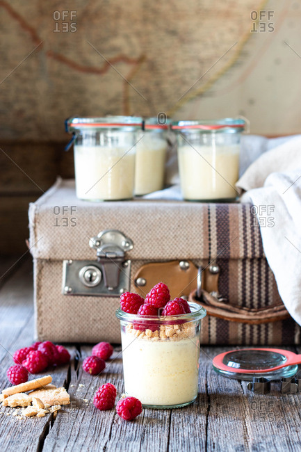 Composition of old suitcase and glass tubs with cheesecake and raspberry placed on wooden table