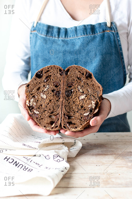 Hands of woman in apron holding rye bread with raisins and nuts