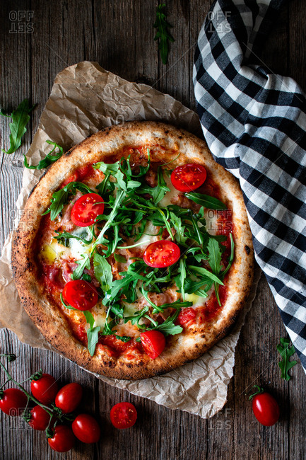 From above delicious pizza with tomato and salad placed with checkered towel on wooden background