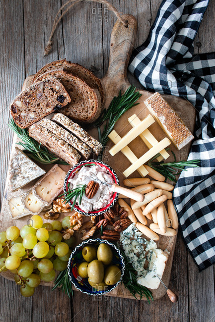 From above composition of fresh rye bread, cheese, grape bunch and olives placed on wooden board