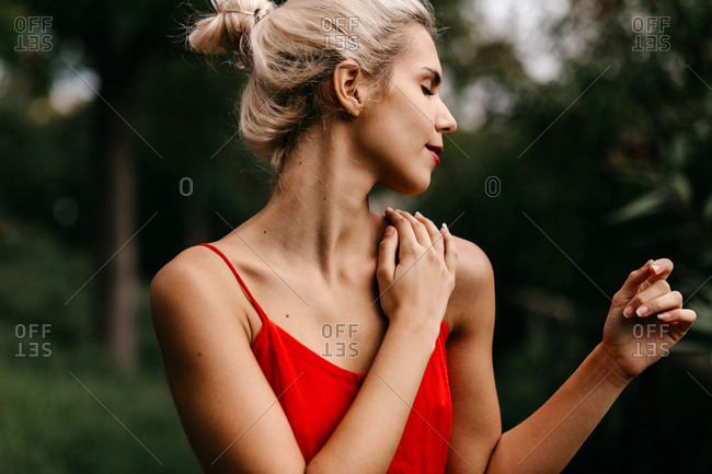 Side view of attractive blonde dressed in red sensually posing and touching her neck with closed eyes among green blooming trees