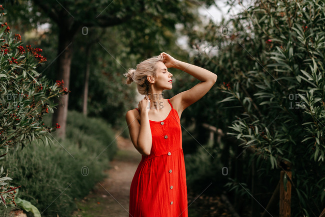 Side view of attractive blonde dressed in red sensually posing with closed eyes among green blooming trees