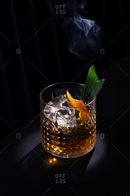 Moody old fashioned cocktail in bar